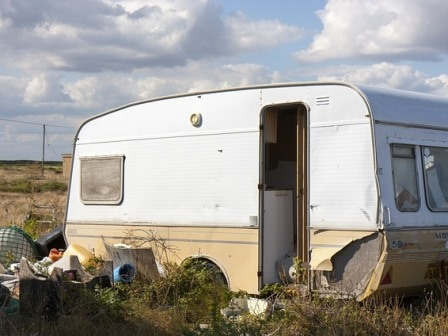 Old caravan surrounded by litter