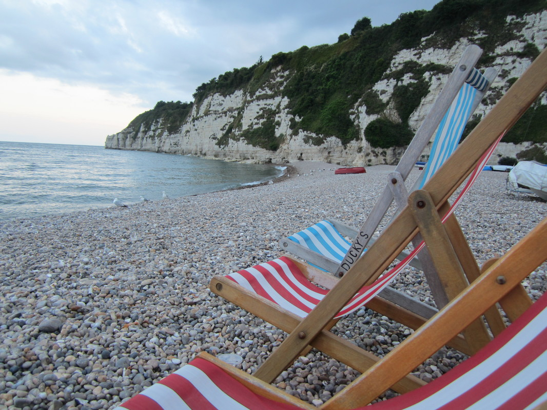 Deckchairs on a shingly beach in Devon